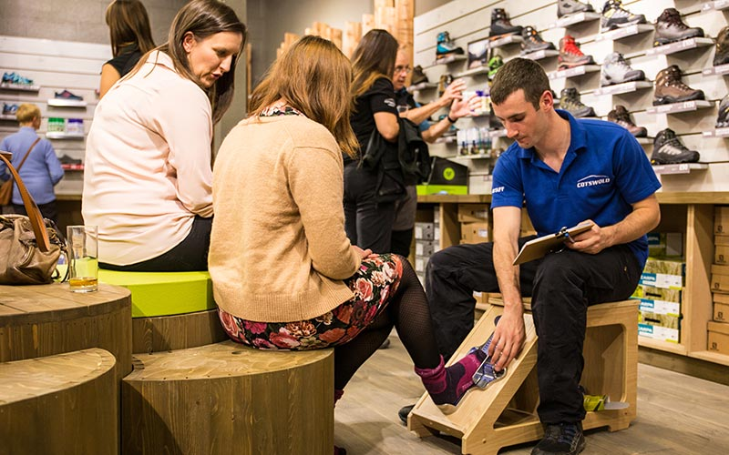 Cotswold outdoor team member helping take size of feet of lady in Webbs Wychbold store